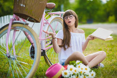 Adolescente que presenta con la bicicleta en el fondo del jardín Imagenes de archivo