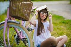 Adolescente que presenta con la bicicleta en el fondo del jardín Imagen de archivo