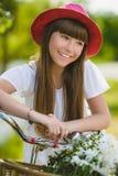 Adolescente que presenta con la bicicleta en el fondo del jardín Fotos de archivo