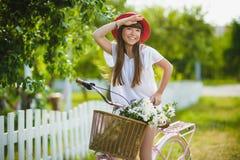 Adolescente que presenta con la bicicleta en el fondo del jardín Fotos de archivo libres de regalías