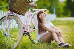 Adolescente que presenta con la bicicleta en el fondo del jardín Foto de archivo