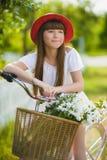 Adolescente que presenta con la bicicleta en el fondo del jardín Imágenes de archivo libres de regalías