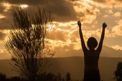 Adolescente que presenta con puesta del sol detrás de las nubes adentro Imágenes de archivo libres de regalías