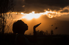 Adolescente que presenta con puesta del sol detrás de las nubes adentro Fotos de archivo libres de regalías