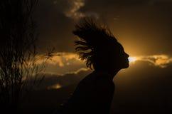 Adolescente que presenta con puesta del sol detrás de las nubes adentro Imagen de archivo libre de regalías
