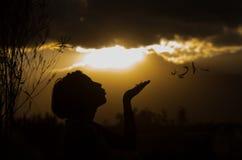Adolescente que presenta con puesta del sol detrás de las nubes adentro Fotografía de archivo libre de regalías