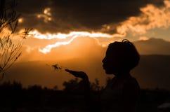 Adolescente que presenta con puesta del sol detrás de las nubes adentro Foto de archivo