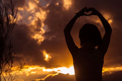 Adolescente que presenta con puesta del sol detrás de las nubes adentro Imagen de archivo