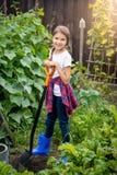 Adolescente que presenta en el jardín del patio trasero con la pala Fotografía de archivo