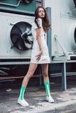 Adolescente que presenta en el vestido blanco y calcetines verdes en la calle Imagenes de archivo