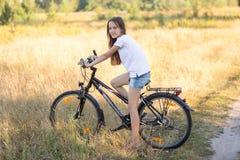 Adolescente que presenta en la bicicleta en campo en el día soleado caliente Imágenes de archivo libres de regalías