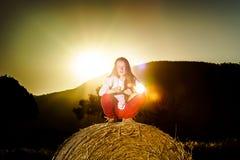Adolescente que presenta en la tarde en pajar, colores de la puesta del sol Fotografía de archivo
