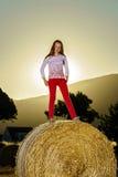 Adolescente que presenta en la tarde en pajar, colores de la puesta del sol Fotografía de archivo libre de regalías
