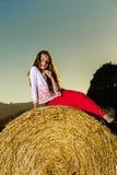 Adolescente que presenta en la tarde en pajar, colores de la puesta del sol Fotos de archivo libres de regalías