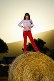 Adolescente que presenta en la tarde en pajar, colores de la puesta del sol Imagen de archivo
