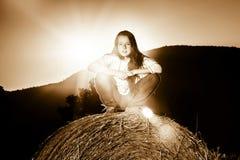 Adolescente que presenta en la tarde en pajar, colores de la puesta del sol Foto de archivo