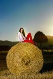 Adolescente que presenta en la tarde en pajar, colores de la puesta del sol Imágenes de archivo libres de regalías