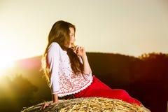 Adolescente que presenta en la tarde en pajar, colores de la puesta del sol Imagen de archivo libre de regalías