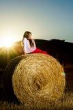 Adolescente que presenta en la tarde en pajar, colores de la puesta del sol Imagenes de archivo