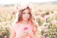 Adolescente que presenta en rosaleda Fotografía de archivo libre de regalías