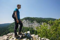 Adolescente que presenta en un acantilado muy alto Foto de archivo