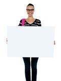 Adolescente que presenta la cartelera en blanco blanca Imagenes de archivo