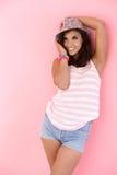 Adolescente que presenta sobre fondo rosado Foto de archivo