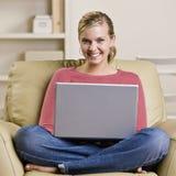 Adolescente que pulsa en la computadora portátil en silla Foto de archivo libre de regalías