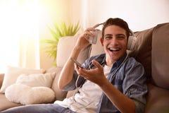 Adolescente que ríe con los auriculares que se sientan en el sofá que mira strai Fotos de archivo libres de regalías