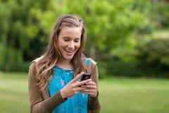 Adolescente que recibe un texto en su teléfono móvil Foto de archivo