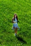 Adolescente que recolecta las flores en campos verdes Imagen de archivo