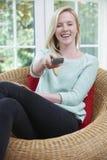 Adolescente que relaja y que ve la TV en casa Imagen de archivo