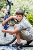 Adolescente que repara su bici, neumático roto cambiante Imágenes de archivo libres de regalías