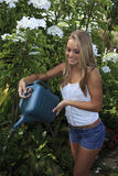 Adolescente que riega su jardín Fotos de archivo