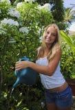Adolescente que riega su jardín Imagenes de archivo