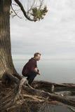 Adolescente que ruega en soledad cerca del lago Imagen de archivo libre de regalías