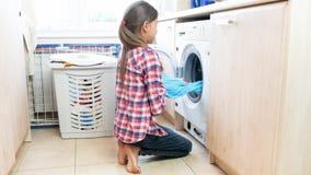 Adolescente que saca la ropa limpia mojada de hacer juego que se lava en el lavadero Imagen de archivo