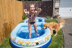 Adolescente que salpica en piscina inflable Imagen de archivo