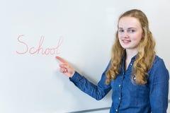 Adolescente que señala en la escuela de la palabra escrita en el tablero blanco Imagen de archivo