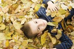 Adolescente que se acuesta con las hojas alrededor. Fotos de archivo libres de regalías