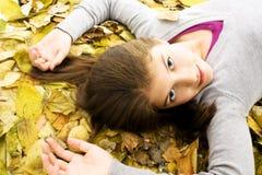 Adolescente que se acuesta con las hojas alrededor. Fotografía de archivo libre de regalías