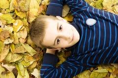 Adolescente que se acuesta con las hojas alrededor. Imagenes de archivo