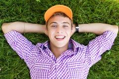Adolescente que se acuesta en hierba Imagen de archivo