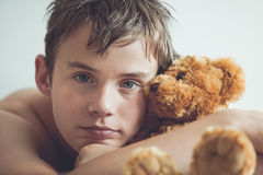 Adolescente que se acurruca con Brown Teddy Bear Imagenes de archivo