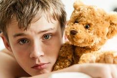 Adolescente que se acurruca en cama con Brown Teddy Bear Fotografía de archivo libre de regalías