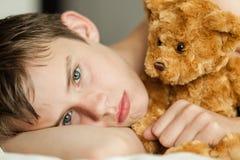 Adolescente que se acurruca en cama con Brown Teddy Bear Fotografía de archivo