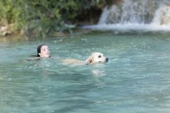Adolescente que se baña en un lago con su perro Fotos de archivo libres de regalías