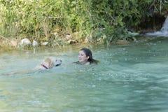 Adolescente que se baña en un lago con su perro Imágenes de archivo libres de regalías