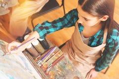 Adolescente que se centra en lona de arte mientras que pinta Imagenes de archivo