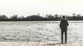 Adolescente que se coloca al borde de un embarcadero cerca del agua Imagen de archivo libre de regalías